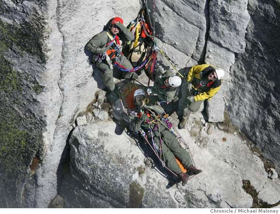 "On a narrow ledge along the granite wall of Fairview Dome, SAR members from left Eric Gabriel, Dov Bock and Keith Lober wait for a rope from the helicopter to transport acting ""victim"" SAR member John Dill (on stretcher).  Members of Yosemite National Park�s Search and Rescue Team (SAR) participate in ""short-haul"" training - using a helicopter to haul a SAR member on the end of a 150 foot rope to rescue stranded or injured climbers or hikers. Members of SAR are required to re-certify every 90 days for short haul rescue. On this day, they practiced short haul on Fairview Dome in the Tuolumne meadows area of Yosemite  Every year, the park�s Search and Rescue team deals with over 200 incidents and the park has, on average, about 12 fatalities per year. At least 10-14 short haul type rescues take place each year. Those can range from taking a climber off of El Cap to hauling out an injured backcountry hiker. Their helicopters log over 350 hours in the air every season. Photo by Michael Maloney / San Francisco Chronicle ***Eric Gabriel, Dov Bock, Jason Ramsdell, John Dill MANDATORY CREDIT FOR PHOTOG AND SF CHRONICLE/NO SALES-MAGS OUT Photo: Michael Maloney"