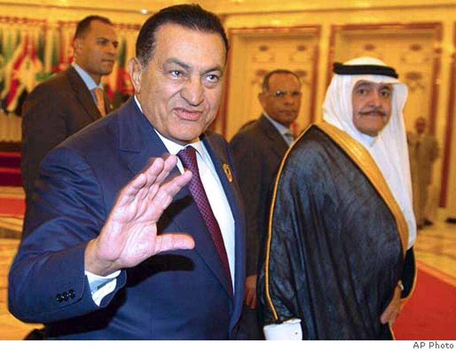 Egyptian President Hosni Mubarak gestures as he arrives at Jeddah International airport, Thursday, Dec. 8, 2005, to attend the Islamic nations summit held in Mecca, Saudi Arabia. Former Saudi Oil Minister Hisham Nazer, right, looks on. (AP Photo) Photo: Ap