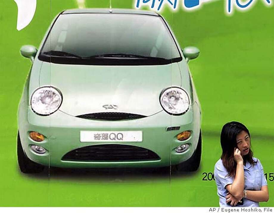 ** FILE ** A woman talks on mobile phone near an advertisement of Chinese automeker Chery Automobile Co.'s QQ mini-car Friday, July 15, 2005 in a Shanghai, China file photo. General Motors Corp. said it reached a settlement resolving all legal disputes with Chinese automaker Chery Automobile Co. GM had accused Chery of pirating the design of its Spark minicar, which looks similar to the Chery QQ, and had filed lawsuits trying to prevent Chery from selling the car in various markets, including Asia and Eastern Europe. (AP Photo/Eugene Hoshiko, File) Ran on: 12-09-2005  A woman talks on a phone near an advertisement for a car by Chinese automaker Chery. Photo: EUGENE HOSHIKO
