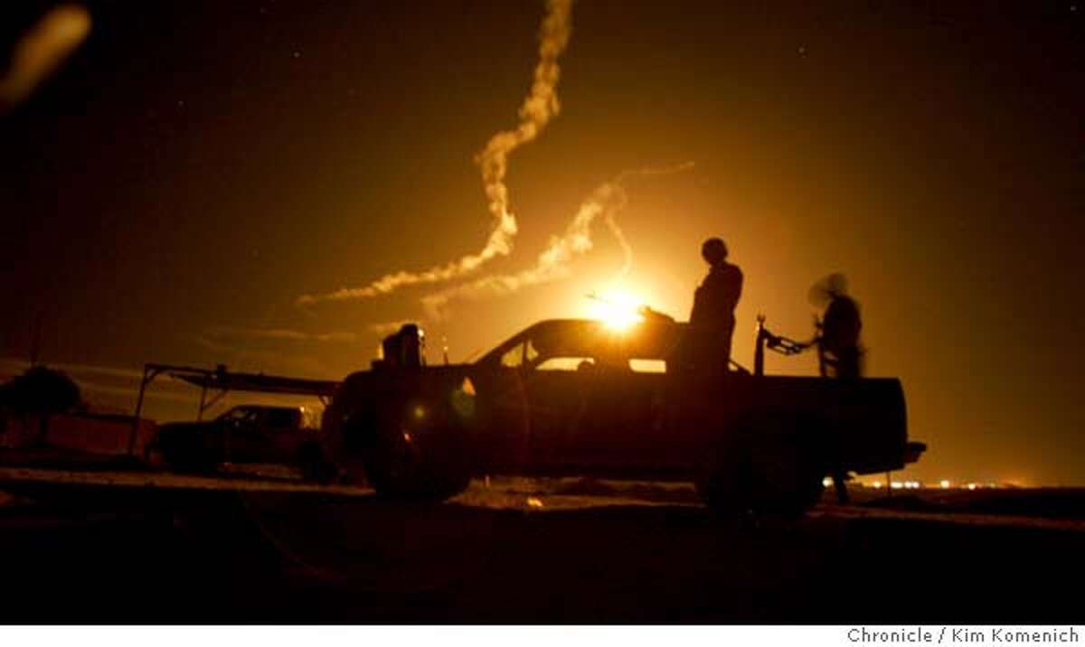 IRAQ09_RAID_0228_KK.JPG Illumination rounds turn the 3:45 am sky into day as an Iraqi police pickup stands guard at a field detention site in Qadessiya. Two companies from the Army's 2-7 Infantry Battalion of the First Brigade, Third Infantry Division stand by as backup as Iraqi Army and Iraqi Police forces launch a major counterinsurgency raid in Qadessiya, a town north of Tikrit. This is likely 2-7 Commander Lt. Col. Todd Wood's last major operation in the Tikrit area. San Francisco Chronicle Photo by Kim Komenich 12/8/05