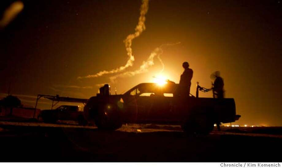 IRAQ09_RAID_0228_KK.JPG  Illumination rounds turn the 3:45 am sky into day as an Iraqi police pickup stands guard at a field detention site in Qadessiya. Two companies from the Army's 2-7 Infantry Battalion of the First Brigade, Third Infantry Division stand by as backup as Iraqi Army and Iraqi Police forces launch a major counterinsurgency raid in Qadessiya, a town north of Tikrit. This is likely 2-7 Commander Lt. Col. Todd Wood's last major operation in the Tikrit area. San Francisco Chronicle Photo by Kim Komenich  12/8/05 Photo: Kim Komenich