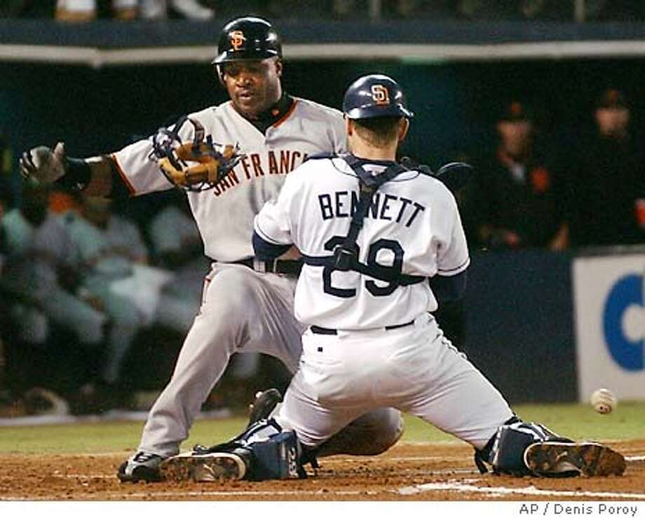 San Francisco Giants' Barry Bonds slides into home as the ball pops out of the glove of San Diego Padres catcher Gary Bennett during the first inning Wednesday, Sept. 10, 2003, in San Diego. Bonds scored on a single by Edgardo Alfonzo. (AP Photo/Denis Poroy) Photo: DENIS POROY