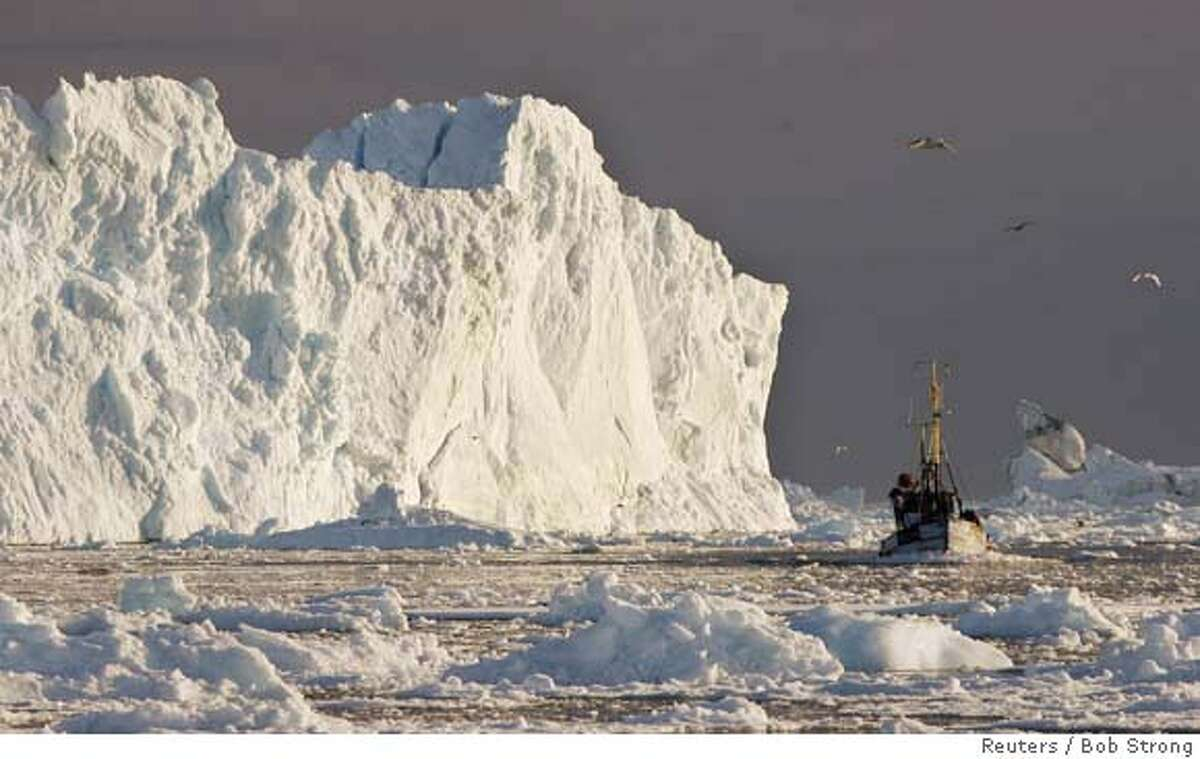 A fishing boat sails past a large iceberg at the mouth of the Jakobshavns ice fjord near Ilulissat in this photo taken May 15, 2007. Picture taken May 15, 2007. REUTERS/Bob Strong (GREENLAND) Ran on: 06-02-2007 Fishing boat passes iceberg at mouth of Jakobshavns fjord near Ilulissat, midway up Greenlands west coast, in this photo taken May 15.