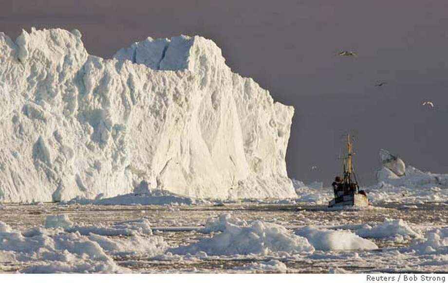 A fishing boat sails past a large iceberg at the mouth of the Jakobshavns ice fjord near Ilulissat in this photo taken May 15, 2007. Picture taken May 15, 2007. REUTERS/Bob Strong (GREENLAND)  Ran on: 06-02-2007  Fishing boat passes iceberg at mouth of Jakobshavns fjord near Ilulissat, midway up Greenland's west coast, in this photo taken May 15. Photo: BOB STRONG