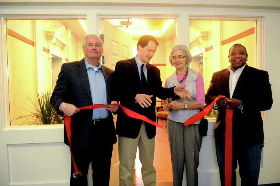 From left, Paul Settelmeyer, distric 2 representative town meeting; U.S. Rep. Jim Himes, D-Conn.; Bernadette Settelmeyer, commissioner of the housing authority; and Tony Johnson, executive director of Greenwich housing authority, at the grand opening ribbon cutting event of the reading room at McKinney Terrace, an affordable senior housing development Sunday, March 18, 2012. Photo: Helen Neafsey / Greenwich Time