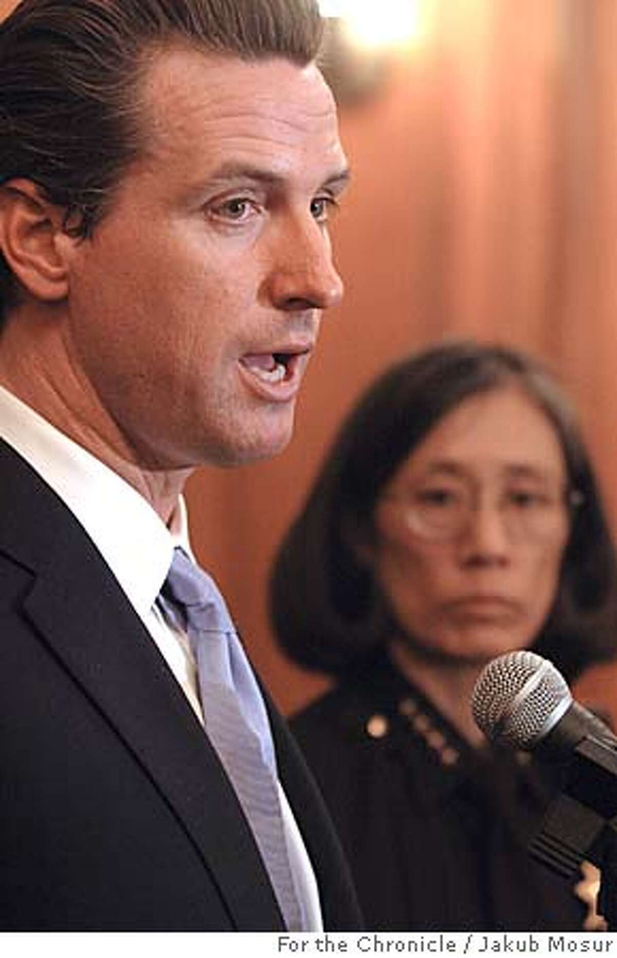Mayor Gavin Newsom faces reporters with Chief of Police Heather Fong, right, Wednesday, Dec. 7, 2005, in San Francisco, where they announced that one police officer was suspended and more than a dozen others faced discipline after making videos parodying life on the force that used racist, sexist and homophobic stereotypes, according to Newsom and Fong. (AP Photo/The Chronicle, Jakub Mosur) ** MANDATORY CREDIT MAGS OUT **