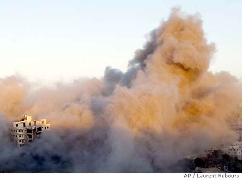 Smoke raises from a building, left, as it is blown up by Israeli forces in an army operation against Palestinian militants in the southern West Bank city of Hebron Tuesday Sept. 9, 2003. Israeli troops surrounded the seven-story apartment building early Tuesday, searching for wanted militants inside. Two bodies were brought out of the building by the forces and also a 12-year-old Palestinian boy was killed during the exchange of fire , hospital officials and witnesses said. (AP Photo/Laurent Rebours) Photo: LAURENT REBOURS