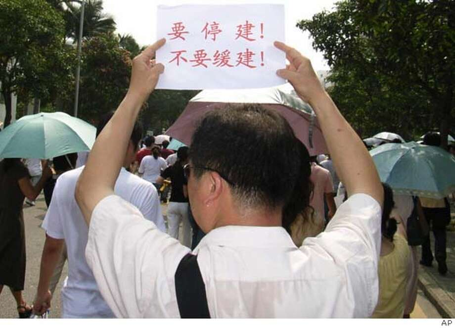 "A protester holds up a sign which reads ""Must stop construction, Not suspend Construction"" during a demonstration against a chemical plant in Xiamen, southeastern China, Friday, June 1, 2007. Protesters rallied against a chemical plant in southeastern China on Friday, even after the local government suspended construction following a mobile phone text message campaign calling attention to pollution dangers and health risks. (AP Photo) ** CHINA OUT ** ** CHINA OUT ** Photo: AP"