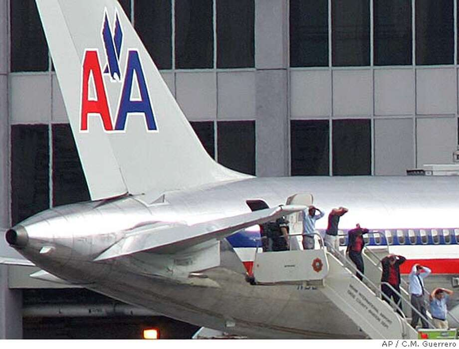 Passengers, with hands on their heads, from American Airlines flight 924 leave the plane after arriving at Miami International Airport from Colombia Wednesday, Dec. 7, 2005, in Miami. A passenger who claimed to have a bomb in a carry-on bag was shot and killed by a federal air marshal Wednesday on a jetway to the American Airlines plane that had arrived from Colombia, officials said. No bomb was found in the bag, a U.S. official said. (AP Photo/El Nuevo Herald, C.M. Guerrero) ** MAGS OUT ** Photo: C.M.GUERRERO