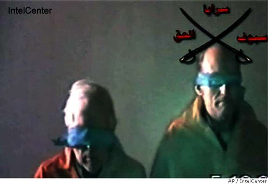 "This still image made from video and released Wednesday, Dec. 7, 2005 by IntelCenter, a government contractor that does support work for the U.S. intelligence community, shows hostages Briton Norman Kember, left, and American Tom Fox. The Swords of Righteousness Brigade released a new video Wednesday showing Kember and Fox, their hands chained and their eyes taped shut. A senior Iraqi official said Wednesday that ""intelligence and security efforts"" were under way to win the release of Western hostages, while kidnappers reportedly extended a deadline for the threatened killing of the four captive peace activists. (AP Photo/IntelCenter) ** THE ASSOCIATED PRESS HAS NO WAY OF INDEPENDENTLY VERIFYING THE CONTENT, LOCATION OR DATE OF THIS VIDEO ** IMAGE MADE FROM VIDEO AND RELEASED WEDNESDAY, DEC. 7, 2005 BY INTELCENTER THE ASSOCIATED PRESS HAS NO WAY OF INDEPENDENTLY VERIFYING THE CONTENT, LOCATION OR DATE OF THIS VIDEO Photo: Ho"
