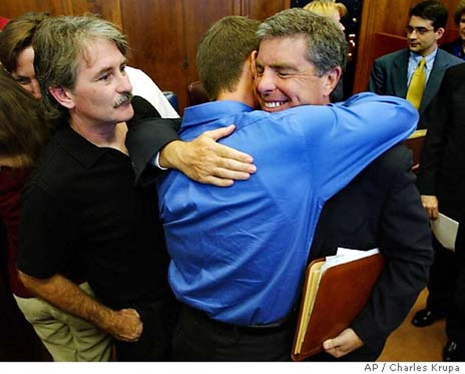Attorney Robert Sherman, right, is hugged by church victim Gary Bergeron, center, and thanked by victim Bernard McDaid, left, after the Boston Archdiocese agreed to settle clergy sex cases at Suffolk Superior Court in Boston, Tuesday, Sept. 9, 2003. The Boston Archdiocese agreed to pay $85 million to more than 500 people who claim Roman Catholic priests sexually abused them, giving victims a long-awaited formal recognition of their pain and the church a chance to move forward from one of the worst scandals in its history. (AP Photo/Charles Krupa) Photo: CHARLES KRUPA