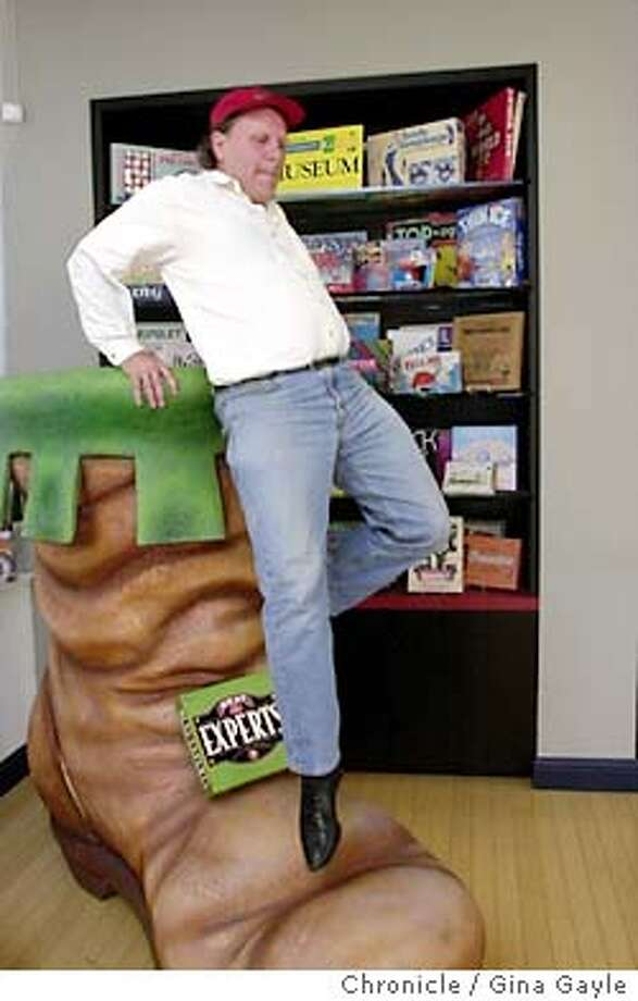 A big kid himself, Bob Moog, the CEO of University Games, climbs out of one of two giant shoes he has in his company's office with vintage board games he has collected over the years on display in the background. The company which he co-founded in 1985 has grown to become what he says is the fifth largest game company in the country. Part of Moog's philosophy is to make games that spur interaction with kids especially between parent and child. 5/20/03 in San Francisco. GINA GAYLE / The Chronicle Photo: GINA GAYLE