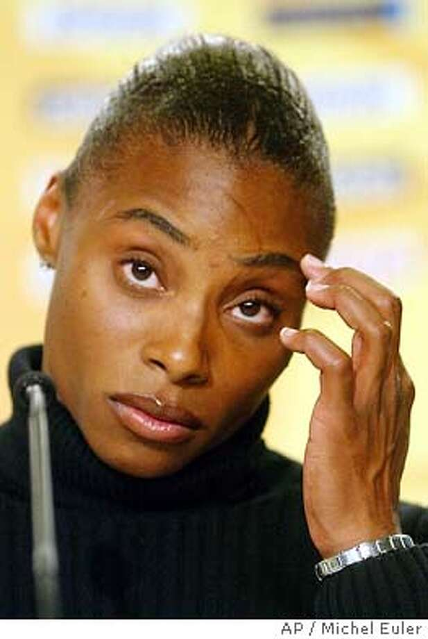 Kelli White of the USA, winner of the gold medal in the Women's 100-meter and 200-meter races at the World Athletics Championships, ponders a question during a press conference at the Stade de France in Saint Denis, north of Paris, in this Aug. 30, 2003 photo. White committed a doping offense at the World Championships and should be stripped of her two gold medals, track and field's governing body ruled Tuesday, Sept. 9, 2003.(AP Photo/Michel Euler) Photo: MICHEL EULER