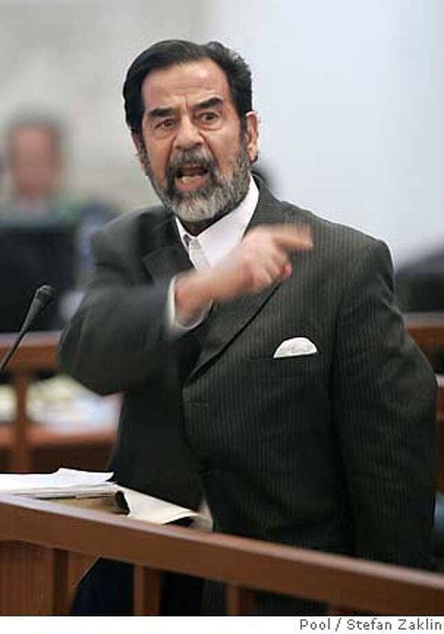 Former Iraqi president Saddam Hussein gestures during his trial held under tight security in Baghdads heavily fortified Green Zone, Tuesday Dec. 6, 2005. Saddam and seven others face charges that they ordered the killing in 1982 of nearly 150 people in the mainly Shiite village of Dujail, north of Baghdad, after a failed attempt on the former dictators life. (AP Photo/Stefan Zaklin, Pool) Photo: STEFAN ZAKLIN