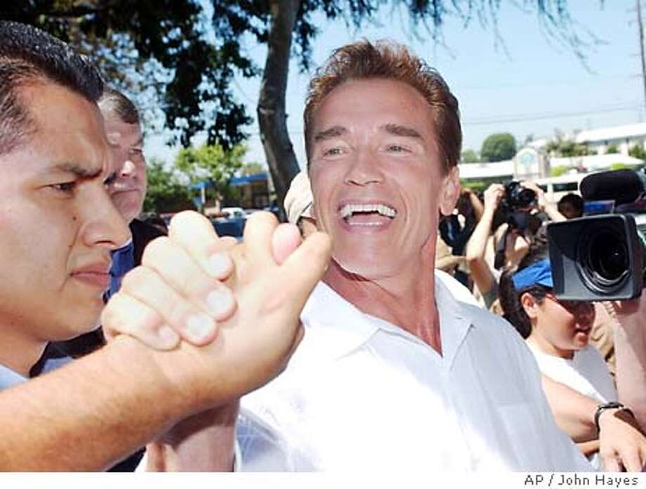 Gubernatorial candidate Arnold Schwarzenegger meets supporters at a softball field in Santa Fe Springs, Calif., Sunday, Sept. 7, 2003. The republican's name will be on California ballots in October as replacement governor if voters recall current Gov. Gray Davis. (AP Photo/John Hayes) Photo: JOHN HAYES