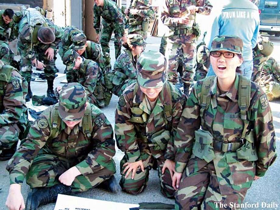 Azia Kim (far right) looks at the camera during an ROTC rifle assembly line training exercise on Oct. 18, 2006. During fall quarter, Kim regularly attended both a military class and lab each week, posing the whole time as a high-achieving Stanford freshman. Mandatory Credit: The Stanford Daily We have permission to use it and are waiting on higher resolution version. Photo: The Stanford Daily