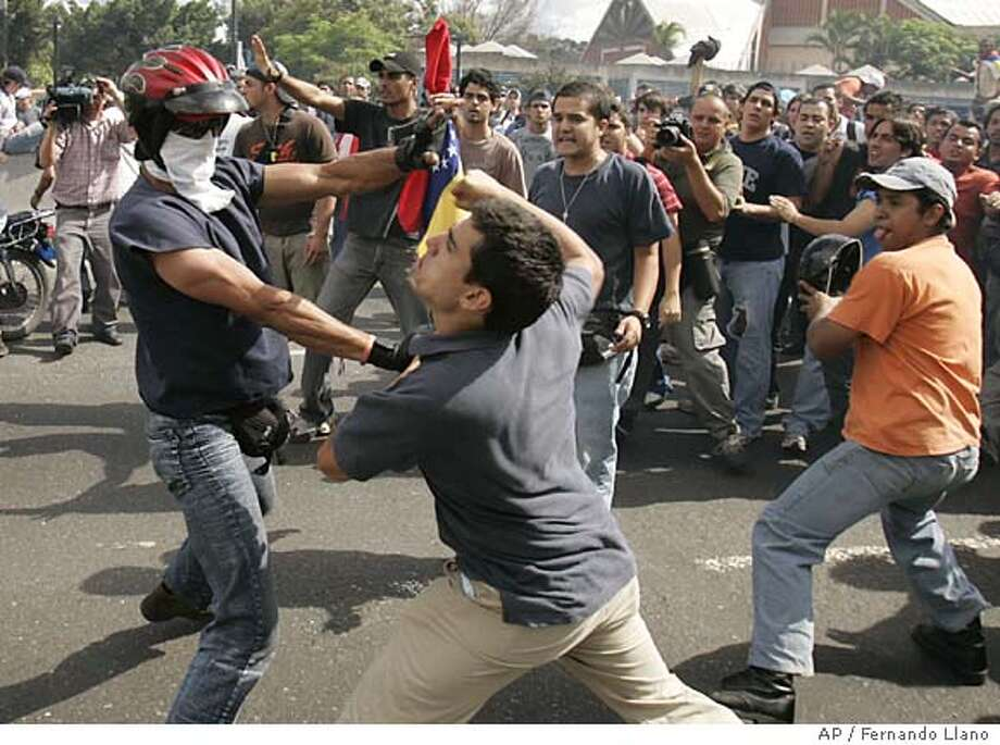 Supporters and opponents of Venezuela's President Hugo Chavez fight during a protest in Caracas, Wednesday, May 30, 2007. Former presidential candidate Manuel Rosales, a top opponent of Chavez demanded the release of jailed protesters as university students poured into the streets for a third day to protest the removal of a leading opposition TV station Radio Caracas Television, RCTV, from the air. (AP Photo/Fernando Llano) Photo: Fernando Llano