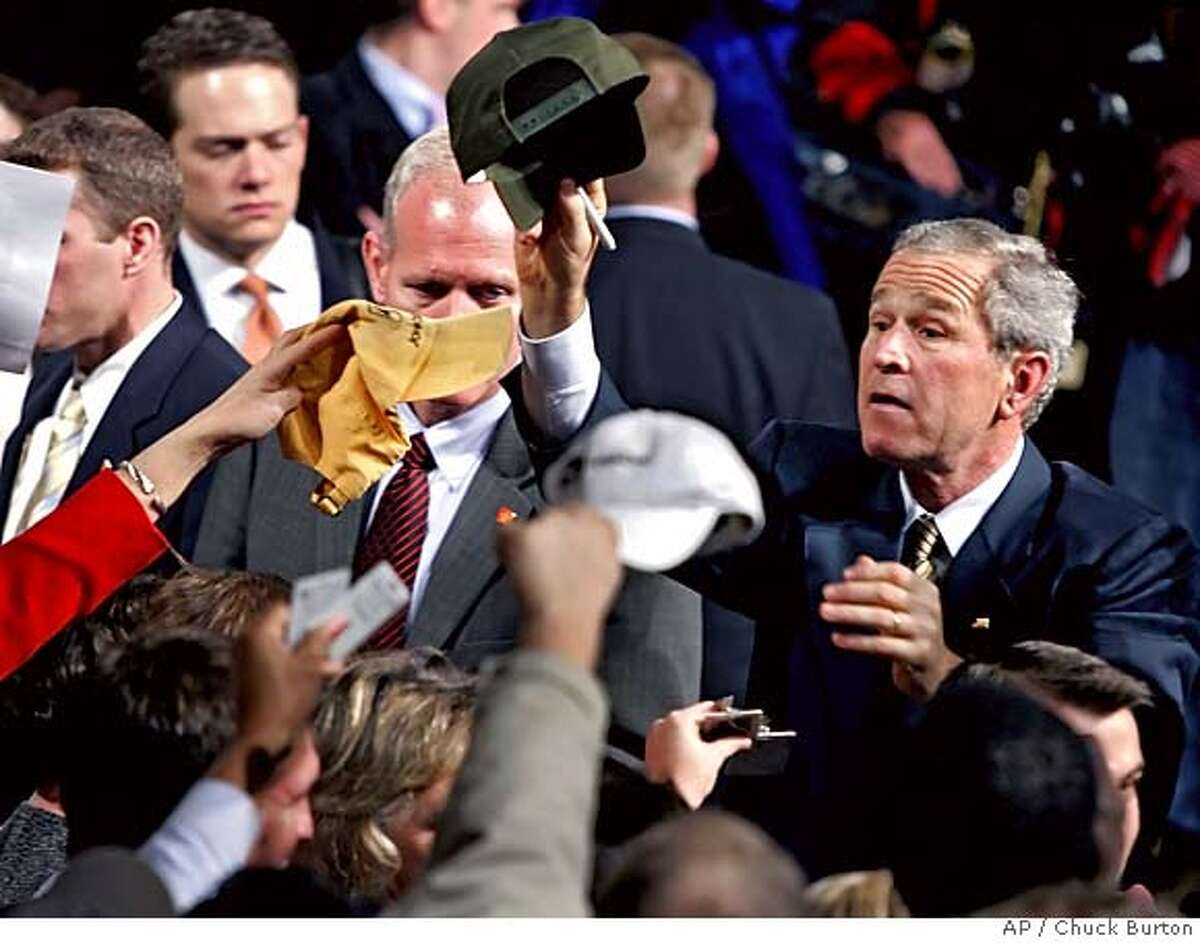 President Bush signs autographs after a speech on the economy at the John Deere-Hitachi plant in Kernersville, N.C., Monday Dec. 5, 2005. (AP Photo/Chuck Burton)