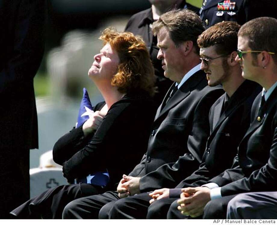The mother of Army Cpl. Christopher E. Murphy, Rosemary Balian, left, hugs the folded flag handed to her during a funeral services for her son, Tuesday, May 29, 2007, at Arlington National Cemetery in Arlington, Va. Murphy, 21, of Lynchburg, Va., a member of the 431st infantry battalion stationed out of Fort Drum, N.Y., was one of four American soldiers killed in an ambush May 12 south of Baghdad, in Iraq. Three more Americans were captured in the pre-dawn attack. As of Sunday, one had been found dead, and the others were still missing. (AP Photo/Manuel Balce Ceneta) Photo: Manuel Balce Ceneta