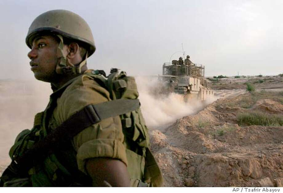 An Israeli armored vehicle drives towards an entry point to the northern Gaza Strip, on the Israel-Gaza border Tuesday, May 29, 2007. Israeli Prime Minister Ehud Olmert and Palestinian President Mahmoud Abbas will sit down together next week to try to halt a two-week-old explosion of violence that has seen southern Israel battered by rockets and Gaza pummeled by airstrikes.(AP Photo/Tsafrir Abayov) Photo: TSAFRIR ABAYOV