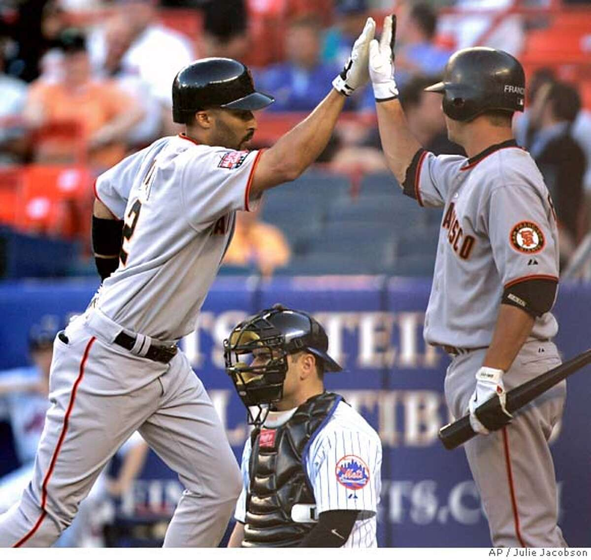 San Francisco Giants' Randy Winn, left, is greeted by Kevin Frandsen at the plate as New York Mets catcher Paul Lo Duca looks on after Winn hit a home run during the first inning in Major League Baseball action Tuesday, May 29, 2007 at Shea Stadium in New York. (AP Photo/Julie Jacobson)