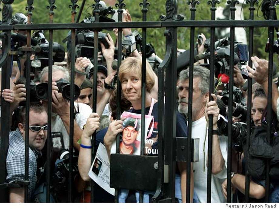 Anti-war protester Cindy Sheehan (C) of Vacaville, CA, holds a portrait of her dead military son Casey, as she stands at the gates of the White House in Washington to ask for a meeting with U.S. President George W. Bush September 26, 2005. U.S. military mother Cindy Sheehan, whose vigil outside Bush's Texas ranch focused attention on the anti-war movement, was arrested on Monday in a sit-in at the White House after refusing to obey police orders to leave. REUTERS/Jason Reed Ran on: 09-27-2005  Photo caption Ran on: 09-27-2005  Photo caption Ran on: 05-30-2007  Cindy Sheehan of Vacaville holds a portrait of her son, Army Spc. Casey Sheehan who was killed in Iraq, at the White House gates. Photo caption Ran on: 05-30-2007  Cindy Sheehan of Vacaville holds a portrait of her son, Army Spc. Casey Sheehan, who was killed in Iraq, at the White House gates. Photo caption Photo: JASON REED