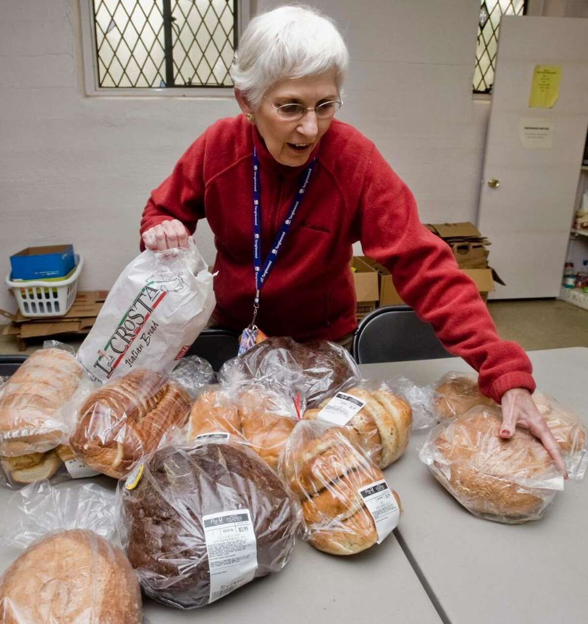 Barbara Lynch, a 5 year volunteer at the food pantry held at St. John's Episcopal Church in Newtown, organizes bread donated from the Big Y supermarket. Tuesday, Nov. 10, 2009