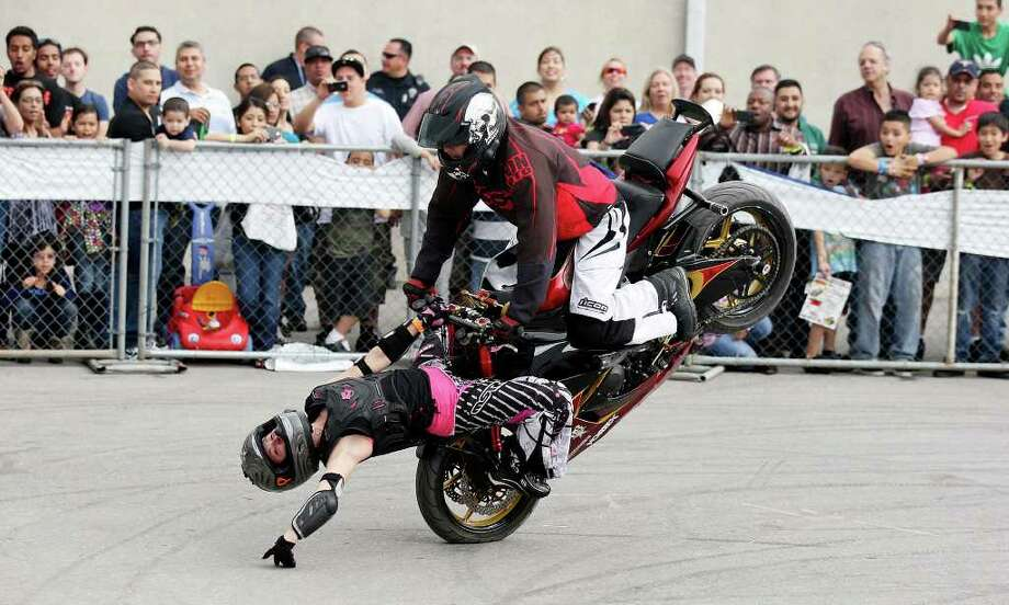 Brandy Arnold (left) and her husband Ken Arnold, from Tulsa, OK, perform during the Busted Knuckles Stunt Tour part of the San Antonio AutoRama & South Texas Motorcycle Show Sunday March 18, 2012 at the Freeman Coliseum. Photo: EDWARD A. ORNELAS, SAN ANTONIO EXPRESS-NEWS / © SAN ANTONIO EXPRESS-NEWS (NFS)