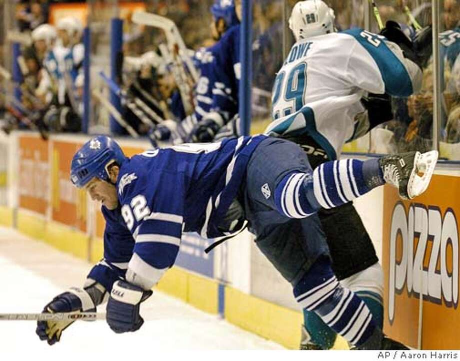Toronto Maple Leafs' Jeff O'Neill, foreground, is hit by San Jose Sharks' Ryane Clowe during first period NHL action in Toronto, Dec. 3, 2005. (AP Photo/Aaron Harris) Photo: AARON HARRIS