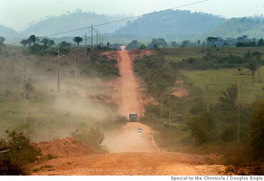"Vehicles create clouds of dust on a highway leading to Brazil's ""middle lands"" through a deforested region of the south of Brazil's Amazonian state of Para, Sept. 30, 2004. As any satellite map can show, there is a direct link of road construction and forest destruction. About 18,000 square kilometers is destroyed each year. Many who come to carve an existence from the forest believe that the Amazon exists to be exploited and point to the USA and Europe as examples. In many ways the federal government promotes this situation with rural projects, highway construction and agrarian reform, while at the same time that it tries to stop it through the environmental agency IBAMA or the Federal Police.(AustralFoto/Douglas Engle) Douglas Engle/Special to The Chronicle Ran on: 05-28-2007  Vehicles produce clouds of dust as they rumble along Brazil's Trans-Iriri highway, which has several settlements but is not on any map.  Ran on: 05-28-2007 Photo: Douglas Engle"