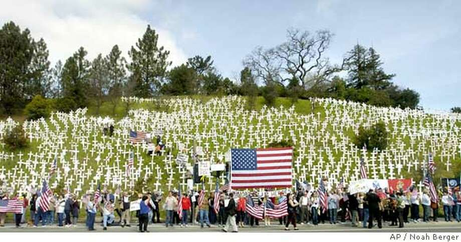 "Demonstrators gather in support of U.S. troops on Thursday, March 8, 2007, in Lafayette, Calif. Protesters, including members of the ""These Colors Dont Run caravan, gathered beneath a hillside where anti-war activists have planted hundreds of crosses representing soldiers killed. The caravan, which began today in San Francisco, is heading across the country to Washington, D.C. (AP Photo/Noah Berger)  Ran on: 03-09-2007  More than 200 demonstrators supporting the Bush administration's conduct of the Iraq war gather to protest a Lafayette hillside display of more than 3,000 crosses representing U.S. soldiers killed in Iraq. Thursday's demonstration on Deer Hill Road was one of the first stops on what the group Move America Forward intends to be a cross-country caravan ending in March 17 in Washington, D.C., where it plans to mount a counter-demonstration to an anti-war protest. Find more photos at sfgate.com.  Ran on: 03-09-2007  More than 200 demonstrators supporting the Bush administration's conduct of the Iraq war gather to protest a Lafayette hillside display of more than 3,000 crosses representing U.S. soldiers killed in Iraq. Thursday's demonstration on Deer Hill Road was one of the first stops on what the group Move America Forward intends to be a cross-country caravan ending March 17 in Washington, D.C., where it plans to mount a counter-demonstration to an anti-war protest. Find more photos at sfgate.com.  Ran on: 03-09-2007 STAND ALONE PHOTO Photo: Noah Berger"