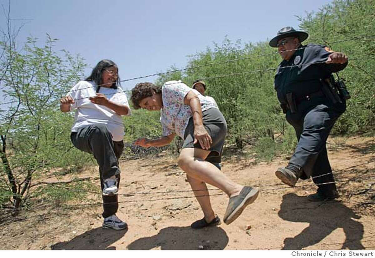 Gloria Chavez (center) climbs through a fence on her property with the help of Harriet Toro (L) and Sgt. Vincent Garcia, a tribal police officer. They are members of the Tohono O'odham Indian Nation, whose reservation straddles the border and struggles with migrant-related crime, trash and medical emergencies. We travel to the Arizona/Mexico border June 20-24 for a series of stories about what the border looks and feels like, how it affects the people and cultures nearby, and how it works from day to day. Chris Stewart / The Chronicle