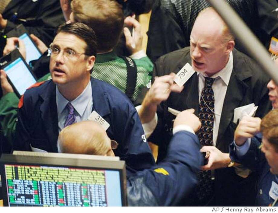 William Techmann, left, a floor official with Citigroup Global Marketing Inc., watches the monitors as Bernard Haddican, right, of 508 Securities Inc., talks to a fellow trader on the floor of the New York Stock Exchange, Thursday, Dec. 1, 2005. Inflation-friendly economic data eased Wall Street's inflation fears and sent stocks sharply higher, giving investors hope that the November rally would continue through year-end. (AP Photo/Henny Ray Abrams) Photo: HENNY RAY ABRAMS