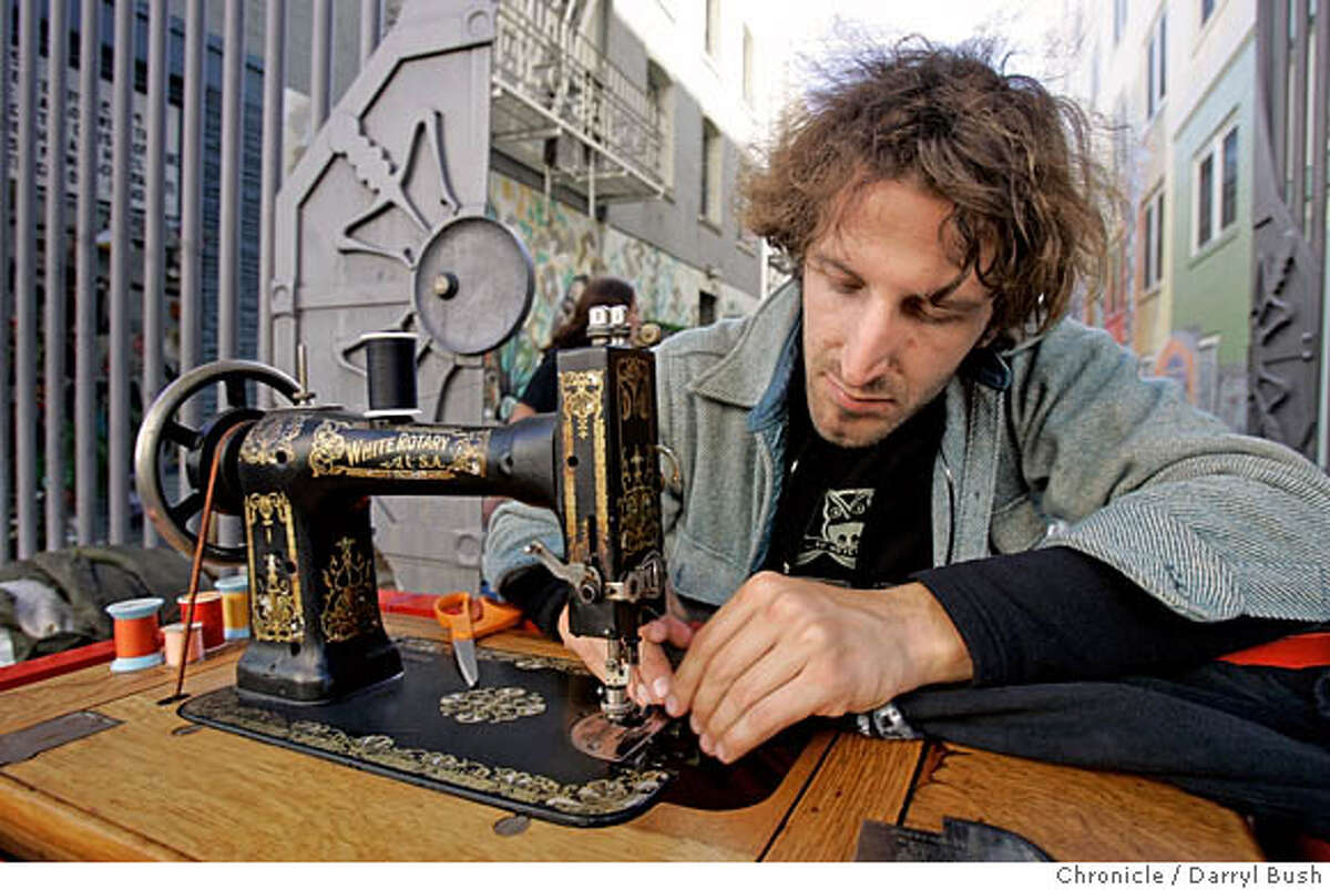 Michael Swaine sews on his sewing machine setup on a cart, on Ellis Street in front of the Cohen Alley gate in the Tenderloin district. Swaine repairs and hems clothes free of charge for anybody who asks. Event on 11/15/05 in San Francisco. Darryl Bush / The Chronicle