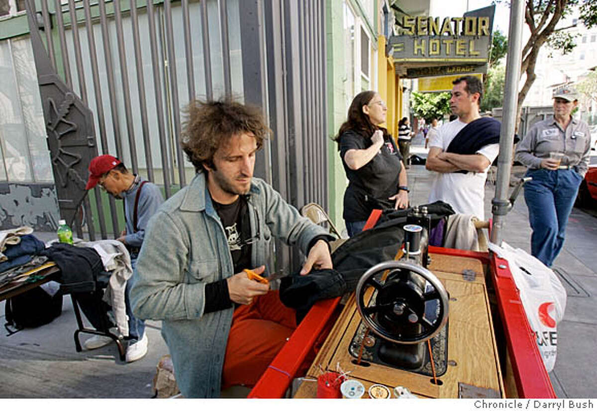 Michael Swaine sews on his sewing machine setup on a cart, with a variety of people hanging out to talk and/or waiting for their clothing, or just walking by on Ellis Street in front of the Cohen Alley gate in the Tenderloin district. Back left is: Toshio Takakura who helps with hand sewing repairs to clothing. Swaine repairs and hems clothes free of charge for anybody who asks. Event on 11/15/05 in San Francisco. Darryl Bush / The Chronicle