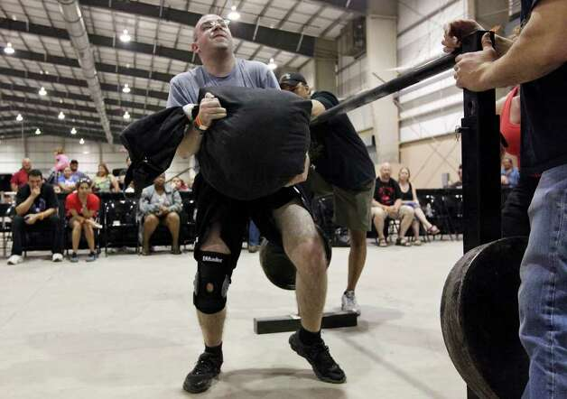 U.S. Army and Marine Corps veteran and wounded warrior Evan  Hudec struggles to lift a 115 pound sandbag during the Shamrock Strength Showdown part of the San Antonio AutoRama & South Texas Motorcycle Show Sunday March 18, 2012 at the Freeman Coliseum. Photo: EDWARD A. ORNELAS, SAN ANTONIO EXPRESS-NEWS / © SAN ANTONIO EXPRESS-NEWS (NFS)
