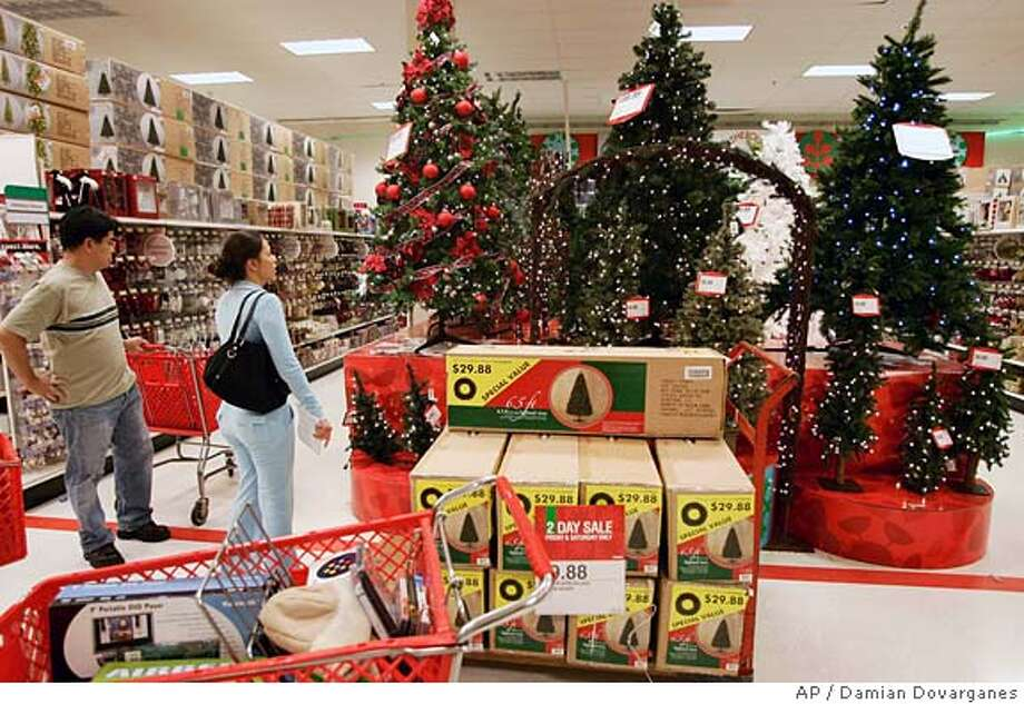 A couple shops for an artificial Christmas tree at the Eagle Rock Target store, Friday, Nov. 25, 2005, in Los Angeles. Bargain shoppers woke up before dawn and headed to the nation's malls and stores Friday, the official start of the holiday shopping season, hoping to snap up early bird specials on items from toys to digital music players. (AP Photo/Damian Dovarganes) Photo: DAMIAN DOVARGANES