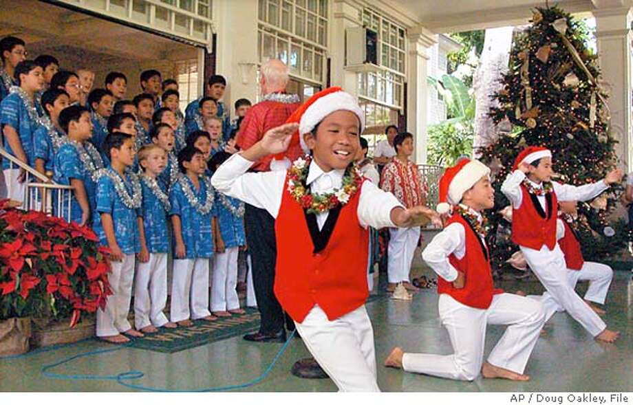 Jonathan Sampaga, 9, foreground, of the Honolulu Boy Choir, dances the hula during an open house at the Washington Place governor's mansion in Honolulu, Sunday, Dec. 22, 2002. (AP Photo/Doug Oakley)  STORY SLUG: Travel Hawaiicalls Photo: DOUG OAKLEY