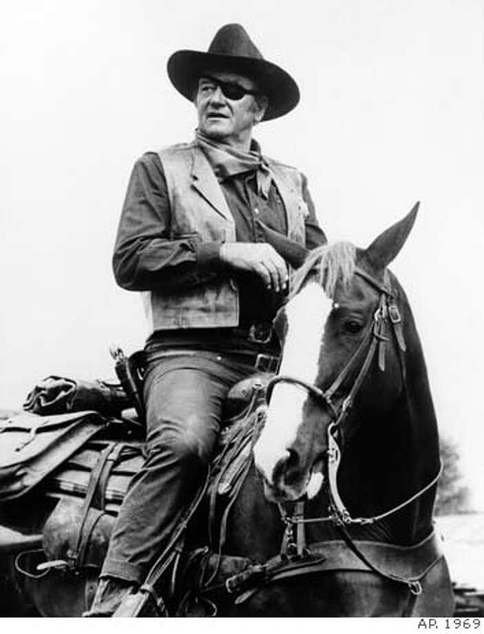 "**FILE**John Wayne appears in a scene from ""True Grit,"" a Hal Wallis production, directed by Henry Hathaway. Wayne won his best-actor Oscar for his role in the 1969 movie. Wayne, born Marion Robert Morrison, would have turned 100 on Saturday, May 26, 2007. He died at the age of 72 of stomach cancer in June of 1979 after a career that spanned more than 170 films. (AP Photo) Photo: AP"