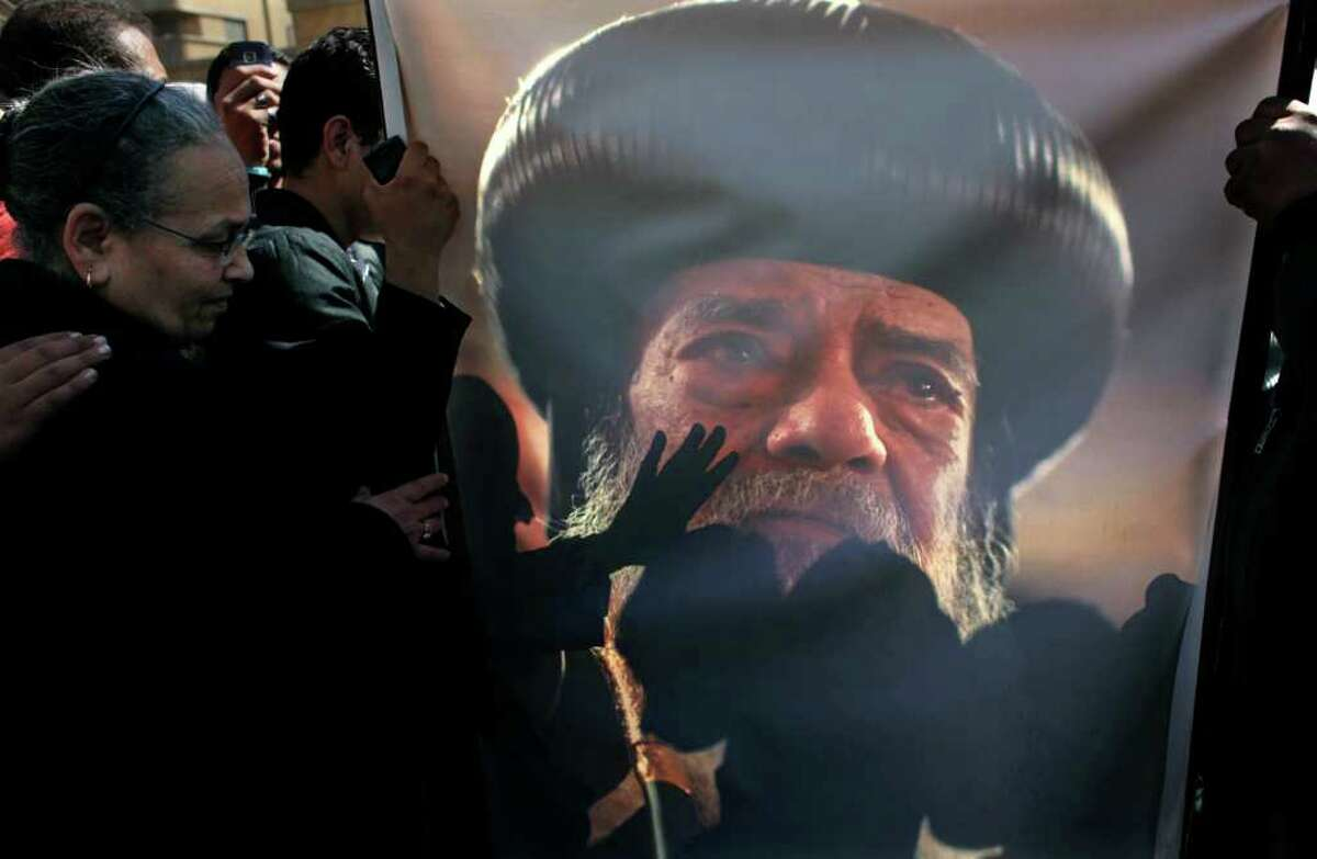 Egyptian Coptic mourners kiss a picture of the ate Pope Shenouda III while gathering outside the Coptic Orthodox Church for the viewing of the body of Pope Shenouda III in Cairo, Egypt, Sunday, March 18, 2012. Pope Shenouda III, the patriarch of the Coptic Orthodox Church who led Egypt's Christian minority for 40 years during a time of increasing tensions with Muslims, died Saturday. He was 88. (AP Photo/Nasser Nasser)