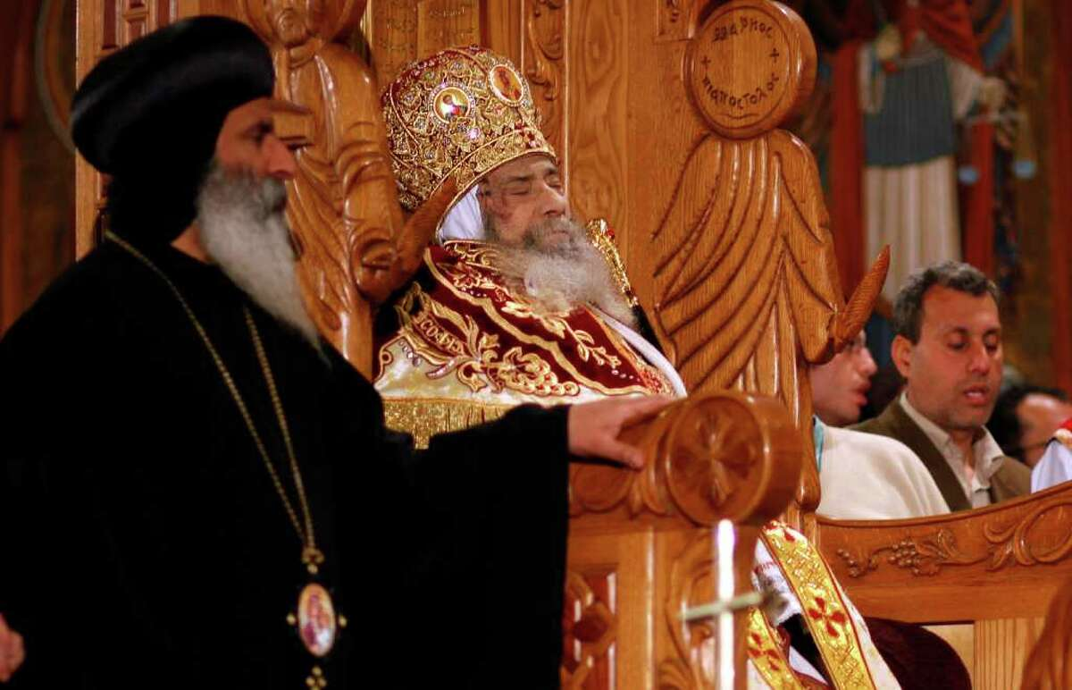 The body of Pope Shenouda III seated on the throne of Mar Morqos or St. Mark, is seen during his funeral at the Coptic Orthodox Church in Cairo, Egypt, Sunday, March 18, 2012. Pope Shenouda III, the patriarch of the Coptic Orthodox Church who led Egypt's Christian minority for 40 years during a time of increasing tensions with Muslims, died Saturday. He was 88. (AP Photo/Khalil Hamra)