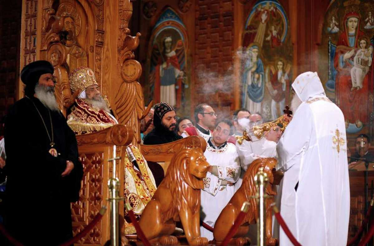 The body of Pope Shenouda III seated on the throne of Mar Morqos, or St. Mark, is seen during his funeral at the Coptic Orthodox Church in Cairo, Egypt, Sunday, March 18, 2012. Pope Shenouda III, the patriarch of the Coptic Orthodox Church who led Egypt's Christian minority for 40 years during a time of increasing tensions with Muslims, died Saturday. He was 88. (AP Photo/Khalil Hamra)