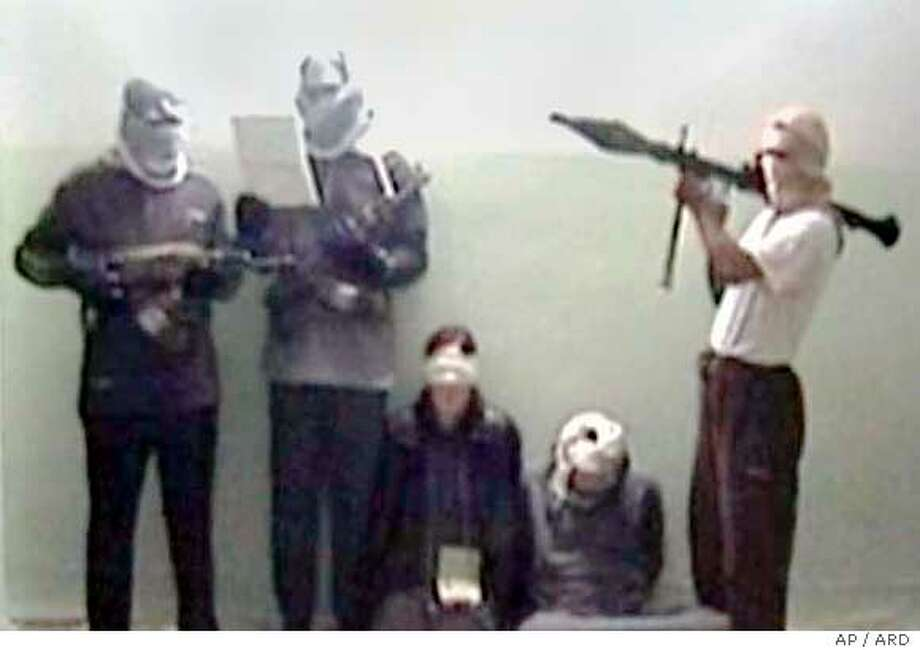 This still from video footage, released by German TV broadcaster ARD on Tuesday Nov. 29, 2005, shows according to the ARD the kidnapped German, Susanne Osthoff, blindfolded 3rd from left, and her driver, 2nd from right, and her captors. ARD reported the frame grab was taken from a video demanding Germany stop any dealings with Iraq's government. (AP Photo/ARD)