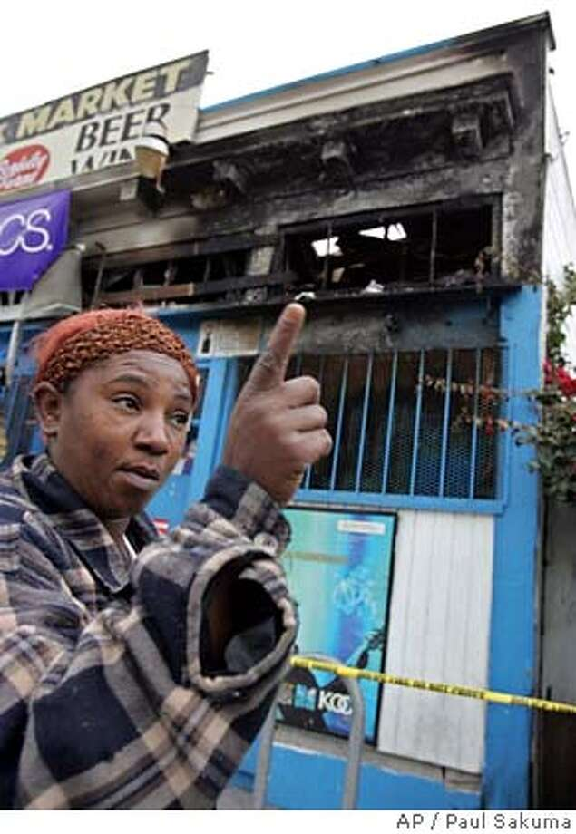 Sharon Jackson points to a liquor store, New York Market, near her home in Oakland, Calif., that was heavily damaged Monday, Nov. 28, 2005, by an apparent arson fire, just days after it was trashed by well-dressed vandals who told the owners to stop selling alcohol to black people, authorities said. Oakland police refused to say whether they believe the blaze at the store was connected to vandalism last week at a nearby liquor store, San Pablo Market, also in Oakland. (AP Photo/Paul Sakuma) Photo: PAUL SAKUMA