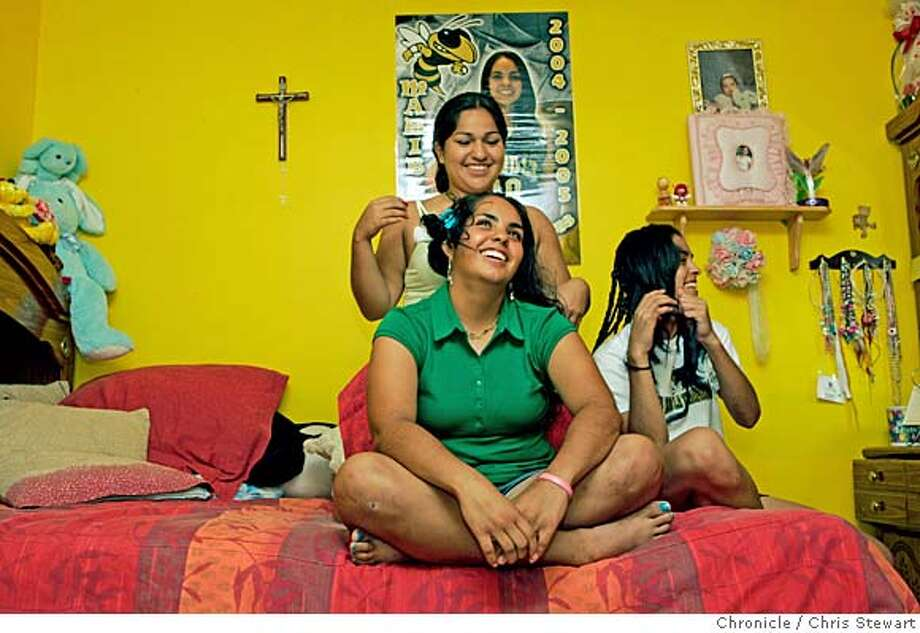 Event on 7/7/05 in McAllen. Maribel Saenz (front), 17, has her hair fussed with by friend Marylu Rodriquez, 16, as Saenz sister Carolina (R), 15, waits her turn in their Elsa, Texas home. We travel to the Texas/Mexico border July 4-8 for a series of stories about what the border looks and feels like, how it affects the people and cultures nearby, and how it works from day to day. This trips focuses on the south-of-the-border maquiladoras and the cross-cultural lifestyle. Chris Stewart / The Chronicle Photo: Chris Stewart