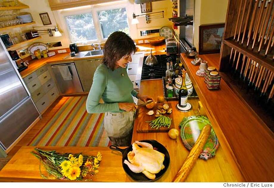 design_kitchens_jones_085_el.JPG  Ann prepping a chicken for the evening meal. Ann Jones's kitchen in Sonoma designed for cooking with open shelves and butcher block counter tops. Photographer:  Eric Luse / The Chronicle names cq from source MANDATORY CREDIT FOR PHOTOG AND SF CHRONICLE/NO SALES-MAGS OUT Photo: Eric Luse