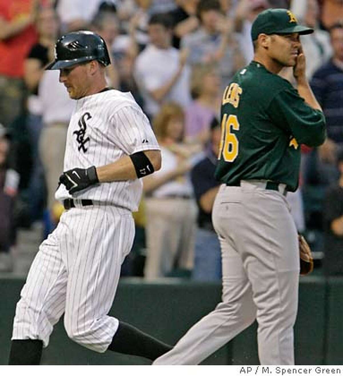Oakland Athletics pitcher Colby Lewis walks back to the mound as Chicago White Sox' Darrin Erstad scores on a two RBI double by Jim Thome during the second inning of a baseball game Tuesday, May 22, 2007, in Chicago. (AP Photo/M. Spencer Green) EFE OUT