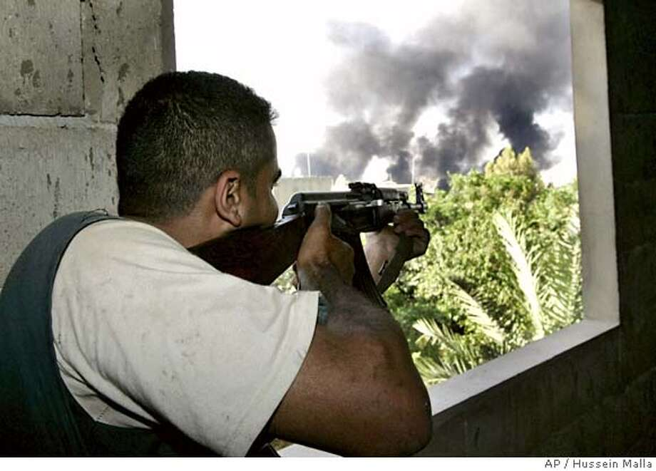 A Lebanese gunman, supporting the Lebanese army, points his AK-47 through a house window towards the Palestinian refugee camp of Nahr el-Bared, during a clashes with fighters from the Fatah Islam militant group, in the northen city of Tripoli, Monday May 21, 2007. Lebanese troops tightened a siege of a Palestinian refugee camp Monday where a shadowy group suspected of ties to al-Qaida was holed up, pounding the camp with artillery a day after the worst eruption of violence since the end of the country's 1975-90 civil war.(AP Photo/Hussein Malla) Photo: HUSSEIN MALLA