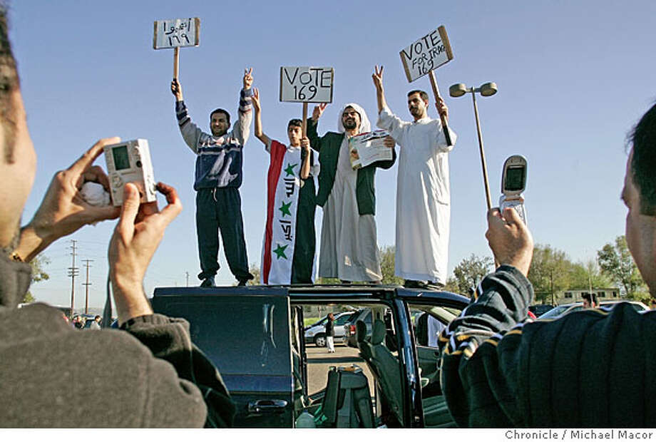 Muhdar Alhassen, of Sunnyvale, joins others, who are climbing to the top of a van to show their excitemnet with the Iraqi vote, l to r-Neema Alhussaini, (Phoenix), Mustafa Jabardi, 14 (Phoenix) wearing an iraqi flag tunic,a friend made, Mudhar Alhassen (Sunnyvale) and Wisam Jabari (Phoenix). A smile for Democracy. Members of the Iraqi Community Center in Sunnyvale, leave at 2 am this morning, drive to Irving,Ca. to vote in the Iraqi election. Follow a group of ex-patriots to one of 5 voting places in the United States as they cast their votes towards Iraq's new government at the, El Toro Marine Corp Air Station, Irvine, Ca. 1/29/05 Irvine, Ca Michael Macor / San Francisco Chronicle Photo: Michael Macor