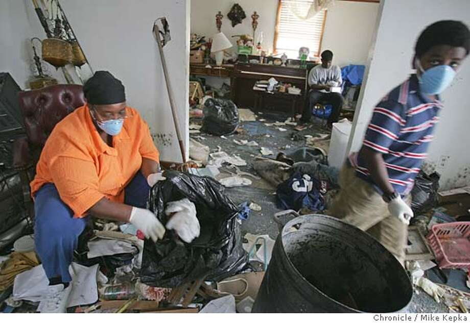 "With the help of her grandson Jonathan Smith, 17, nephew Kevin Ervin, 11, Zadie Alford (left) tries to clean out what's left of her house on the Friday after Thanksgiving on Eganie Street in New Orland's 9th Ward. ""We're just blessed to be alive,"" said Zadie who is now living in an apartment 100 miles away with her husband and 3 grand children in McComb, Mississippi. (zadie can be reached by cell at 504 228-9563)  Three months after the devistaion of Hurricane Katrina residents of of New Orleans 9th Ward, one of the worst neighborhoods hit by the storm, return to salvage whatever they can.  New Orleans on date}. Mike Kepka / The Chronicle Photo: Mike Kepka"